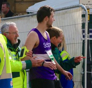 Alex being led off to the St John's Ambulance tent after the race!